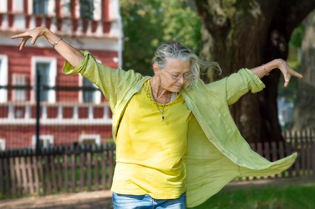 팔을 쭉 뻗은 사슬에 묶이지 않은 노인 여성이 태양과 바람을 즐기는 자유의식으로 춤을 춥니다
