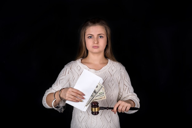 Unchained woman holding gavel and envelope with money
