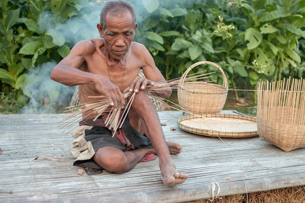 Uncle asian old man with wicker tools.