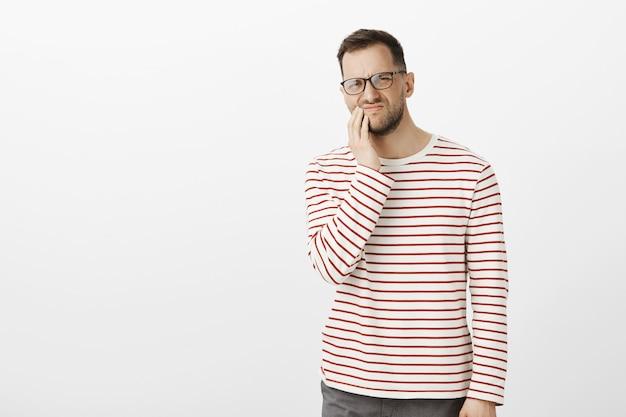 眼鏡をかけた不快な不快な成人男性、口の近くで手を握り、痛みから眉をひそめ、歯痛を感じる