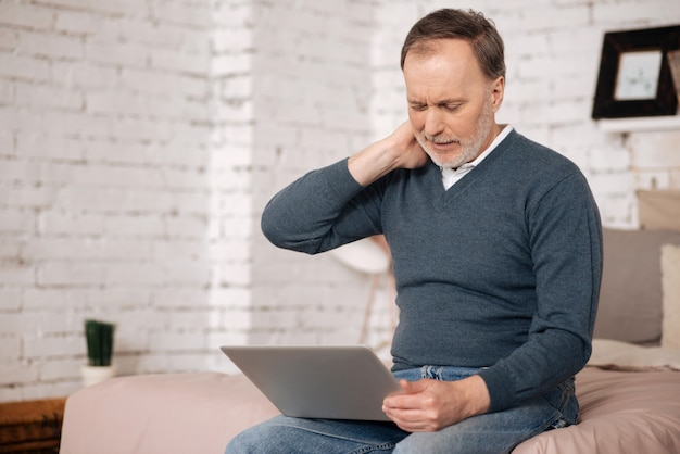 Uncomfortable position. portrait of senior handsome man touching his aching neck while sitting on bed and using laptop.