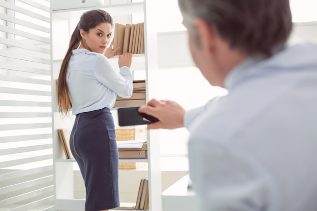 Uncomfortable situation. unhappy cheerless young woman standing near the shelf and putting books there while being photographed