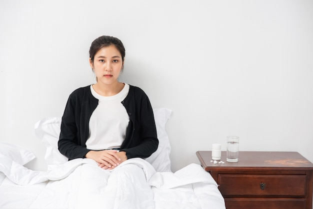 An uncomfortable woman sits on the bed and has medicine on the table.
