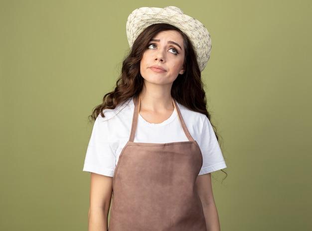 Неуверенная в себе молодая женщина-садовник в униформе в садовой шляпе смотрит в сторону, изолированную на оливково-зеленой стене