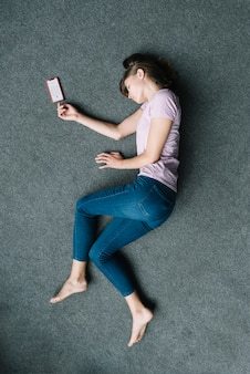 Unconscious woman lying on carpet near mobile phone