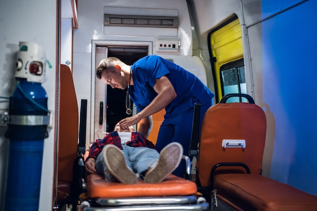 Unconscious woman lying on a stretcher in an ambulance car, a paramedic providing her first aid.