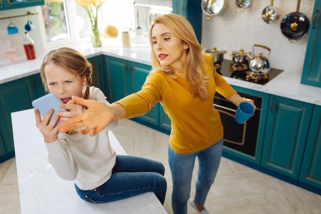 Неконтролируемая светловолосая худенькая девушка держит телефон и плачет, пока мама его забирает