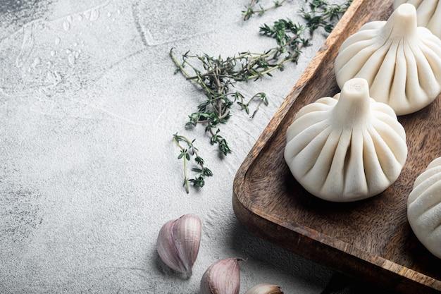 Сырые китайские пельмени баози. набор азиатских пельменей на сером камне