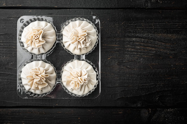 Uncooked baozi chinese dumplings. azian dumplings set, in plastic tray, on black wooden table