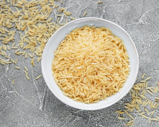 Uncooked basmati rice on a grey concrete surface