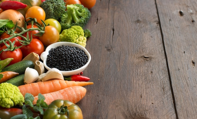Uncooked black lentils in a bowl with vegetables on a wooden table