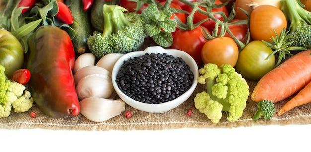 Сырая черная чечевица в миске с овощами, изолированные на белом крупным планом
