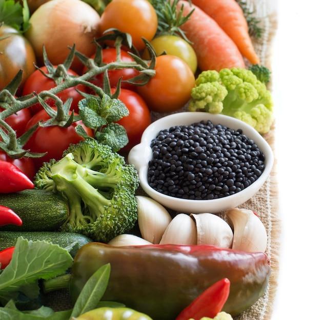 Сырая черная чечевица в миске с овощами, изолированными на белом
