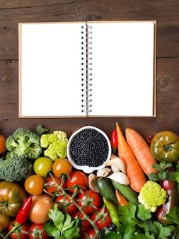 Сырая черная чечевица в миске с овощами на деревянном столе, вид с бумажным блокнотом
