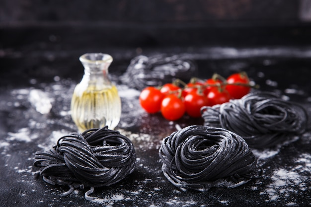 Uncooked black pasta and ingredients for homemade spaghetti italian food