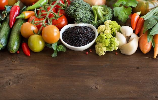 木の上に野菜とボウルに未調理の黒米