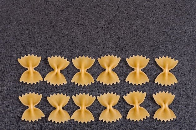 Uncooked bow tie pasta on grey background.