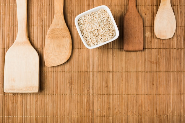Uncooked brown rice bowl with wooden spatulas over the placemat