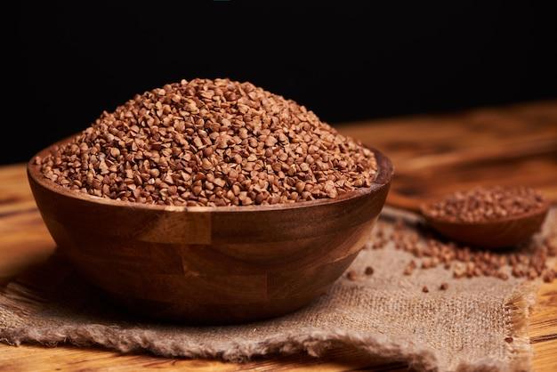 메 밀, 시골 풍 테이블의 전체 나무 숟가락으로 나무 그릇에 생 쌀된 메 밀. 검정색 배경.