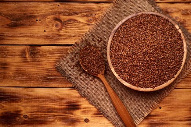메 밀, 나무 배경의 전체 나무 숟가락으로 나무 그릇에 생 쌀된 메 밀. 평면도. 왼쪽의 공간을 복사하십시오.