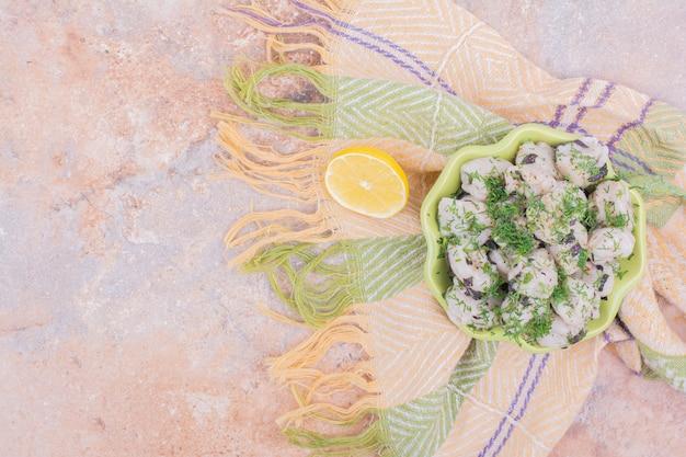 Сырые кавказские хинкали с измельченной зеленью в миске.