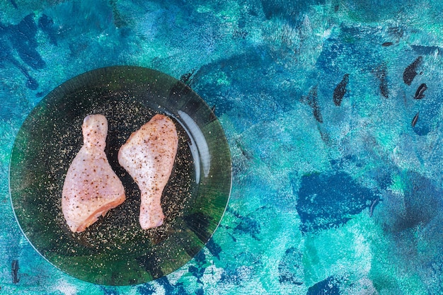 Coscia di pollo cruda marinata in un piatto