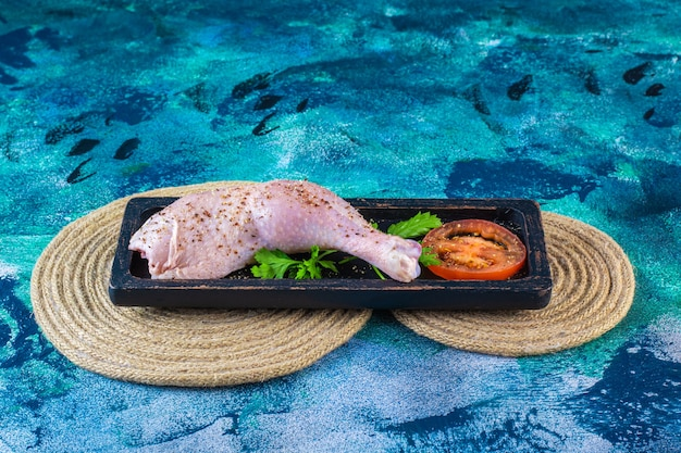 Uncooked chicken drumstick marinated with tomatoes in a wooden plate on the trivet
