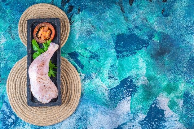 Coscia di pollo cruda marinata con pomodori in un piatto di legno sul sottopentola