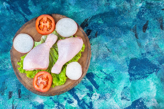 Сырые куриные голени рядом с помидорами, редис на доске