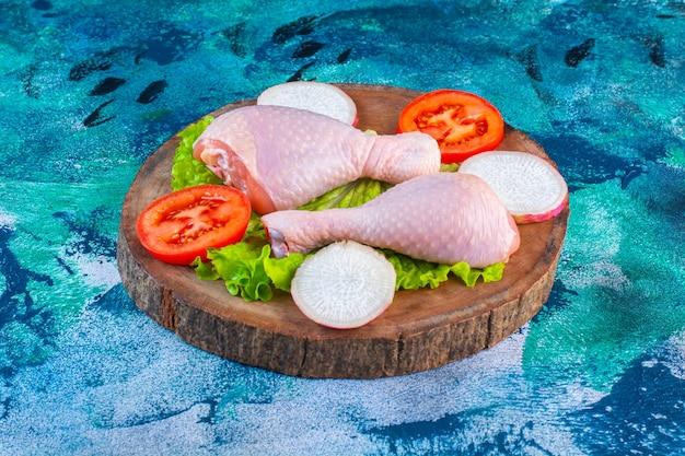Coscia di pollo cruda accanto ai pomodori, ravanello su un tagliere
