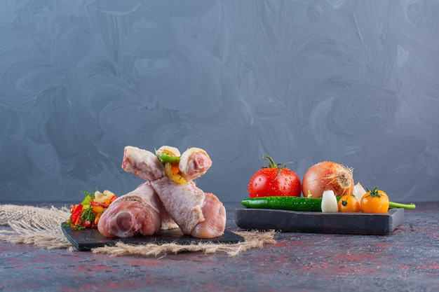 Uncooked chicken drumsticks on black cutting board with vegetables