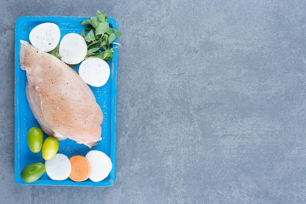 Сырое куриное филе со свежими овощами на синей доске.