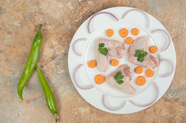 Coscia di pollo cruda con peperoncino sulla superficie in marmo