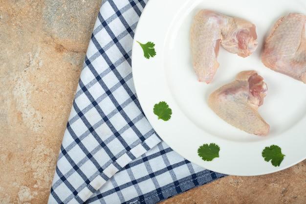 Coscia di pollo cruda con verdure sul piatto bianco