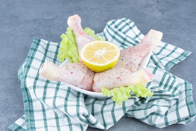 생된 닭 다리와 흰 그릇에 레몬 슬라이스.