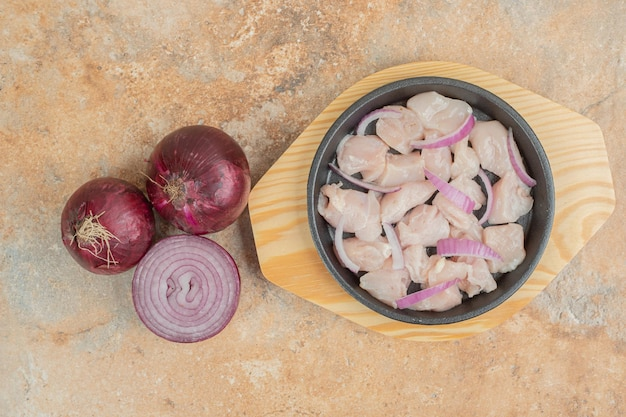 Uncooked chicken legs in dark pan with sliced onion