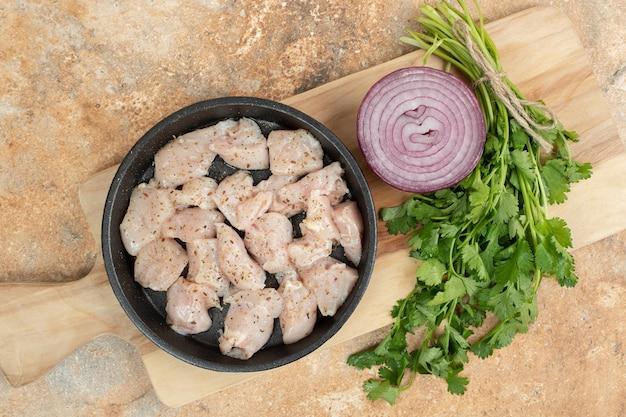 Сырые куриные ножки в темной сковороде с нарезанным луком.