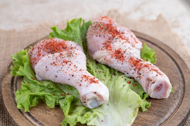 Сырое мясо куриных окорочков с овощами на деревянной доске