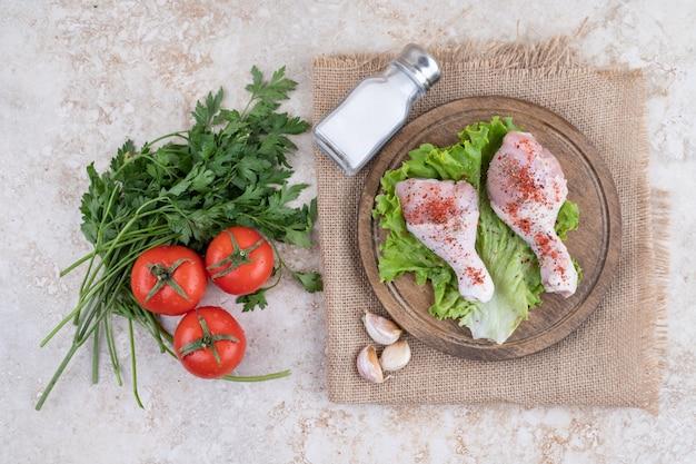 나무 보드에 야채와 함께 요리하지 않은 닭 다리 고기