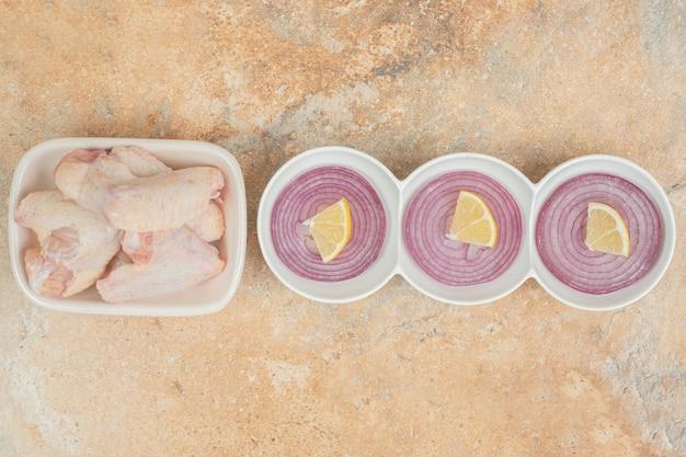 Cosce di pollo crude nel piatto bianco con cipolla affettata