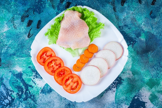 Сырое куриное мясо рядом с помидорами, редисом и морковью на тарелке