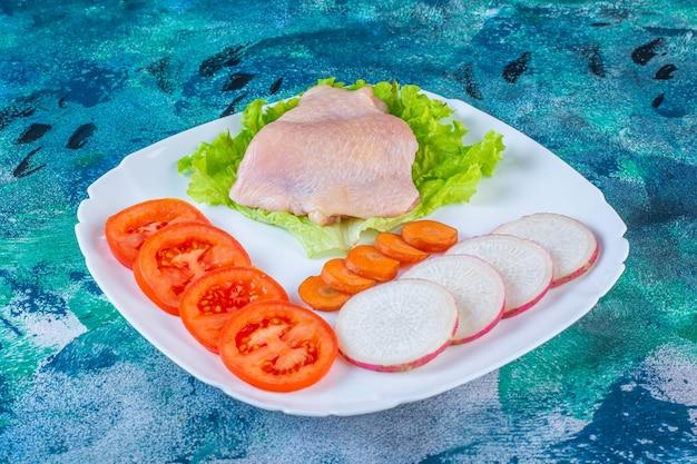Carne di pollo cruda accanto a pomodori, ravanelli e carote su un piatto