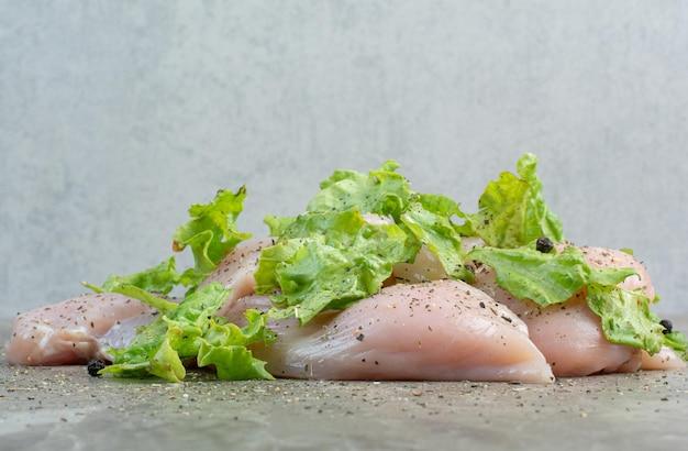 Carne di pollo cruda con pepe e lattuga su fondo di marmo. foto di alta qualità