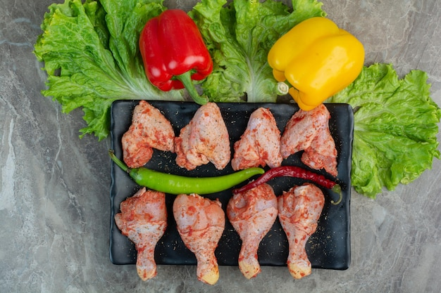 Carne di pollo cruda con spezie su piatto scuro. foto di alta qualità