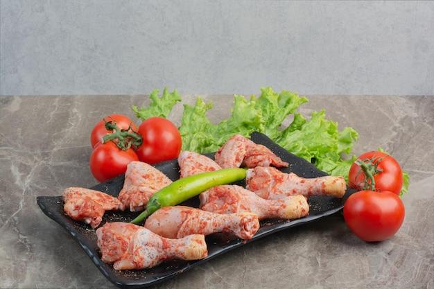 어두운 접시에 향신료와 함께 생 쌀된 닭고기. 고품질 사진