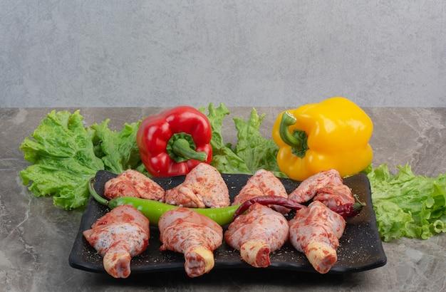 어두운 접시에 향신료와 함께 요리하지 않은 닭고기