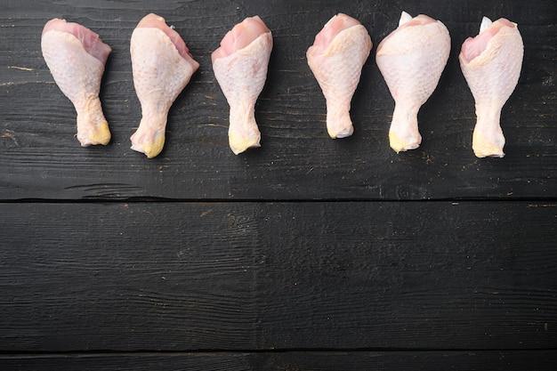 익히지 않은 닭 허벅지 또는 다리, 드럼스틱 세트, 검은 나무 테이블 위에 있는 평면도, 텍스트 복사 공간