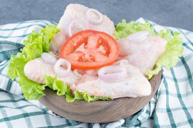 Ali di pollo crude su tavola di legno.