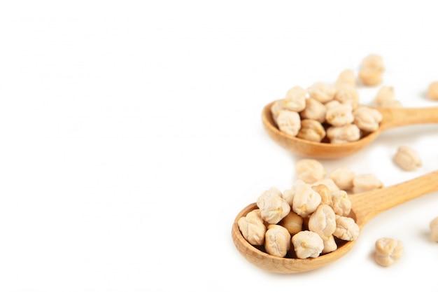 白い背景に分離された木製のスプーンで未調理のひよこ豆。