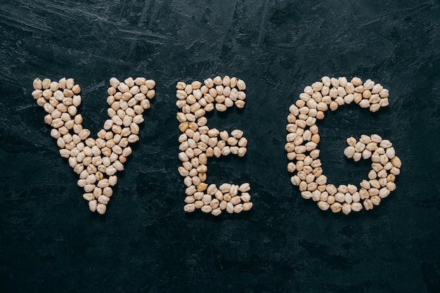 Uncooked chickpeas shaped in letters veg, isolated over dark background.